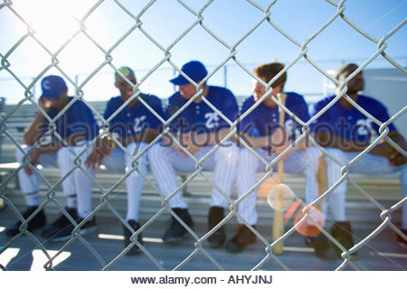 Baseball team sitting on bench in stand during competitive baseball game, view through wire fence, front view lens - Stock Photo