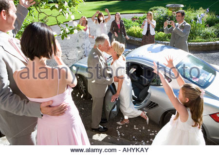 60's couple celebrating marriage next to car surrounded by family throwing petals, - Stock Photo