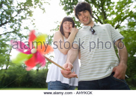 Close-up of windmill held by 20's couple out of focus in background in leafy countryside , - Stock Photo