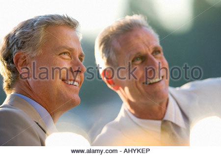 Two mature men sitting at outdoor restaurant table, smiling, close-up - Stock Photo