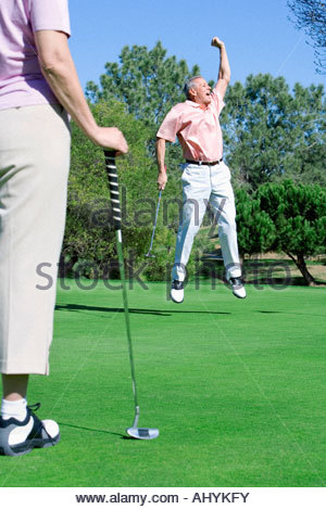 Mature couple playing golf, man punching air in delight at successful putt, woman watching in foreground - Stock Photo
