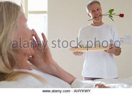 Mature man bringing wife breakfast in bed, carrying tray, holding single red rose between teeth - Stock Photo
