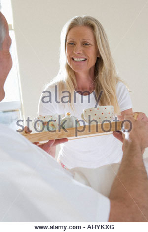 Mature man bringing wife breakfast in bed, carrying tray, woman smiling - Stock Photo