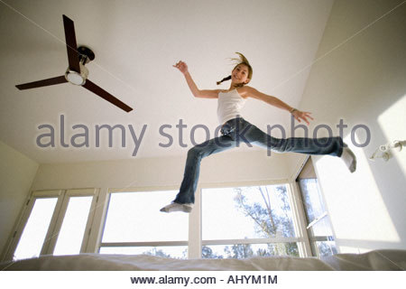 Girl  jumping up and down on bed, mirroring shape of electric ceiling fan, smiling, portrait, low angle view - Stock Photo