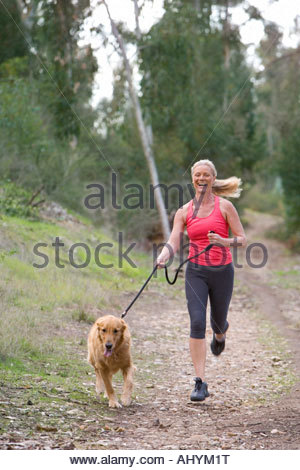 Active senior woman, in pink sports vest and leggings, running with golden retriever along woodland path, laughing, - Stock Photo