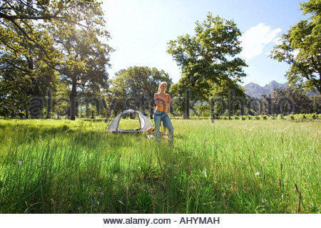 Young woman standing in mid-distance near incomplete dome tent on camping trip in woodland clearing, arms folded - Stock Photo