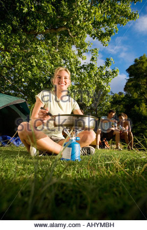 Friends sitting near tent in woodland clearing, focus on young woman cooking food on gas camping stove, smiling, - Stock Photo