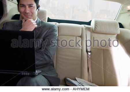 Businessman sitting in backseat of car, wearing mobile phone hands-free device, using laptop, smiling, front view, - Stock Photo