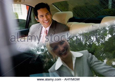 Businessman sitting in backseat of car, greeting businesswoman with smile, reflection of woman standing outside - Stock Photo