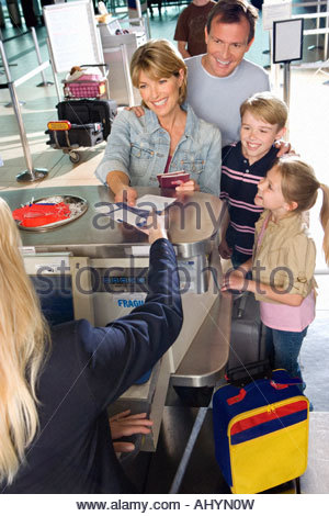 Family checking in at airport check-in counter, woman passing tickets to female airline check-in attendant, smiling - Stock Photo