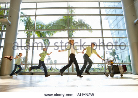 Family running through airport in line, father pushing luggage trolley at front, smiling, side view surface level - Stock Photo