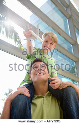 Father carrying son  on shoulders in airport, boy holding toy aeroplane, smiling, front view, low angle view lens - Stock Photo