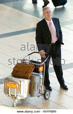 Senior businessman standing with luggage trolley in airport, smiling, elevated view - Stock Photo