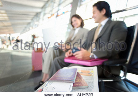 Businessman and woman sitting in airport departure lounge, using laptop, focus on European passport and airline - Stock Photo