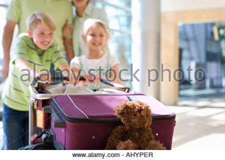 Family pushing luggage trolley in airport, children  smiling, focus on teddy bear and suitcases in foreground - Stock Photo