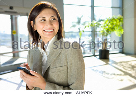 Businesswoman standing in airport, using personal electronic organiser, smiling - Stock Photo