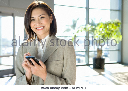 Businesswoman standing in airport, using personal electronic organiser, smiling, portrait - Stock Photo