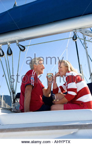 Mature couple, in red jumper and t-shirt, sitting on deck of yacht moored at harbour jetty, drinking white wine, - Stock Photo