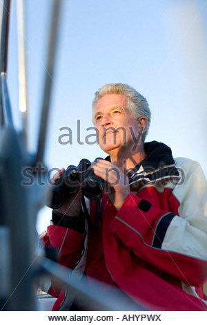 Mature man, in red waterproof jacket, standing on deck of yacht, holding pair of binoculars, smiling - Stock Photo