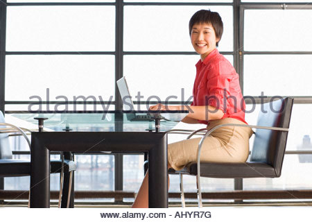 Young woman sitting at table with laptop, smiling, portrait, window in background - Stock Photo
