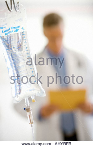 IV bag, male doctor with file in background differential focus - Stock Photo
