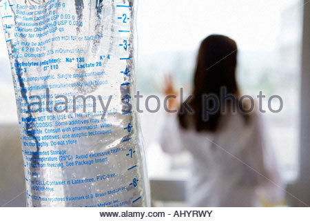 IV bag, young female doctor looking out window in background differential focus - Stock Photo