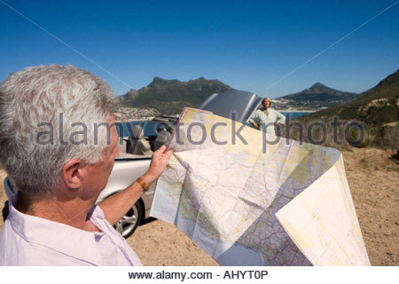 South Africa, Cape Town, mature man looking at map, woman by car in background - Stock Photo