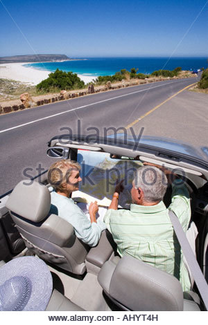 South Africa, Cape Town, senior couple parked on side of road by sea in convertible silver car, looking at map, - Stock Photo
