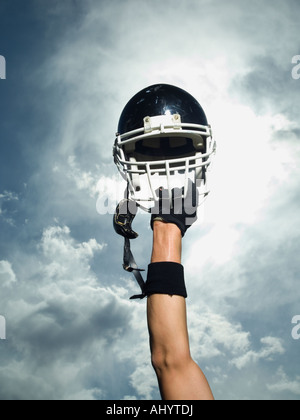 Football player holding helmet in air - Stock Photo