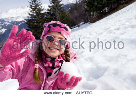 Girl  wearing woolen hat and sunglasses in snow field, holding snow ball, smiling, portrait - Stock Photo