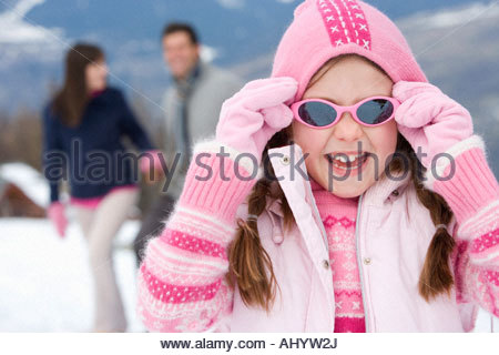 Girl  wearing woolen hat and sunglasses in snow, smiling, portrait, parents in background - Stock Photo