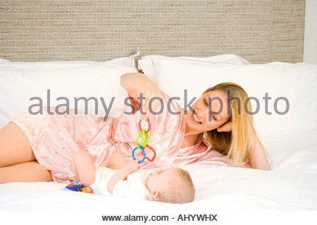Mother and baby girl 9-12 months lying on bed, mother holding toys, smiling - Stock Photo