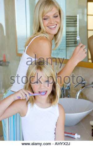 Mother and daughter  brushing their teeth in bathroom, smiling, portrait of girl - Stock Photo