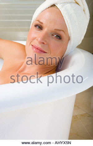 Young woman lying in bath, towel on head, smiling, portrait, close-up - Stock Photo