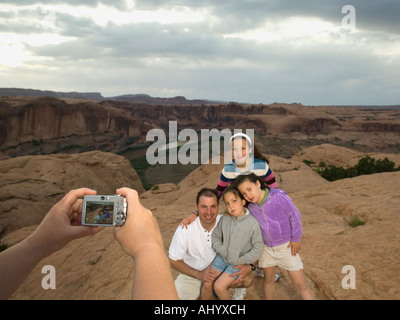 Father and daughters having photograph taken - Stock Photo