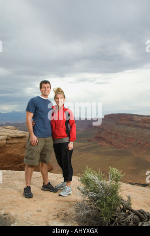 Couple standing at edge of cliff - Stock Photo