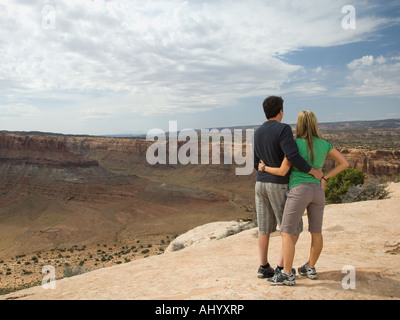 Couple looking over edge of cliff - Stock Photo