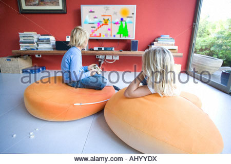 Boy and girl  sitting on bean bags, watching television, rear view - Stock Photo