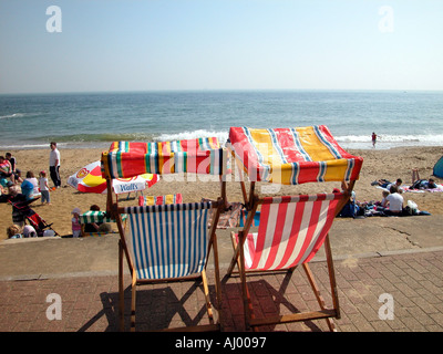 A pair of empty deck chairs on the promenade above a busy spring day Shanklin beach scene, Shanklin, Isle of Wight, - Stock Photo