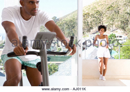 Man on stationary bicycle indoors, woman smiling on balcony in background - Stock Photo