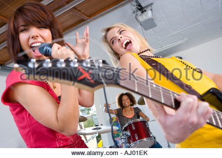 Three teenagers  in garage band, teenage girls singing and playing guitar in foreground - Stock Photo