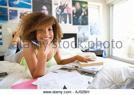 Teenage girl  lying on bed with homework, smiling, portrait - Stock Photo