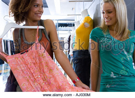 Two young women shopping in clothes store, one holding up dress, smiling - Stock Photo