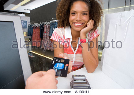 Young woman by counter in clothes shop, smiling, portrait, shop assistant holding out credit card - Stock Photo