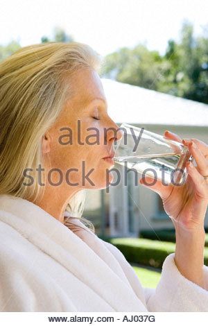 Mature woman wearing white bath robe, drinking  glass of water, side view, close-up - Stock Photo