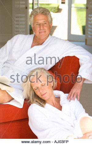 Mature couple wearing white bath robes, woman sitting on floor by man with book on sofa - Stock Photo