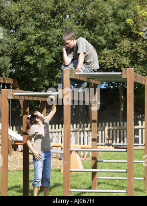 Two teenagers playing on the monkey bars in a children's playground - Stock Photo