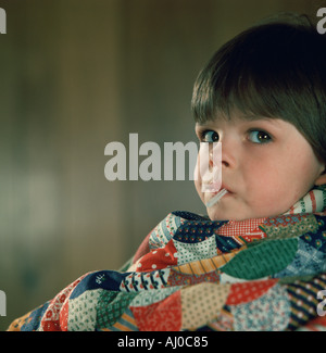 Young boy sits wrapped in a colorful blanket while having his temperature taken with an oral mercury thermometer - Stock Photo