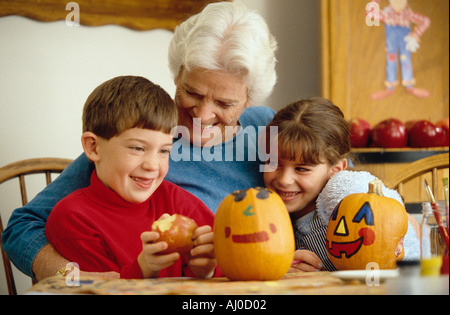 Grandmother hugs her two grandchildren while sitting at a kitchen table decorated with painted Halloween pumpkins - Stock Photo