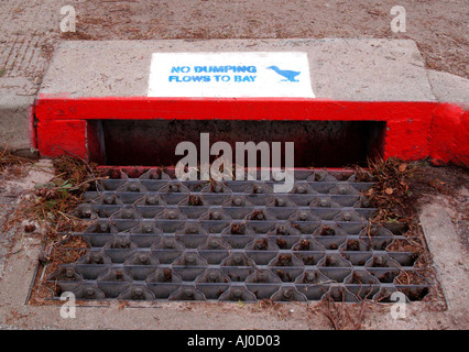 Storm water inlet with NO Dumping Flows To Bay notice painted on it - Stock Photo
